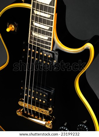 High contrasted part of electric guitar on black - stock photo