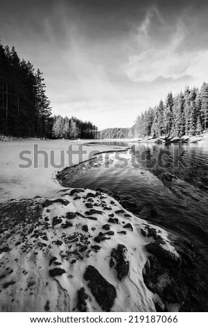 high contrasted vertical black and white winter landscape with frozen high mountain lake  - stock photo