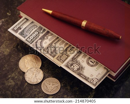 High Denomination US Paper Money Organized within Money Management Book with an Elegant Wooden Pen on top and Silver Coins along side resting on a Polished Green Granite