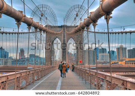 High dynamic range image (HDR) of tourists crossing the Brooklyn Bridge under its strong cables