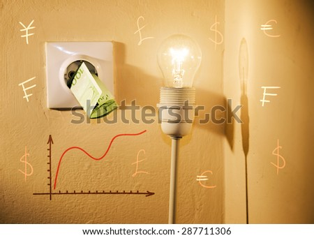 High electric bill concept, euros in power socket, light bulb, increasing graphic chart and world currencies. High contrast image, selective focus on light bulb and bill  - stock photo