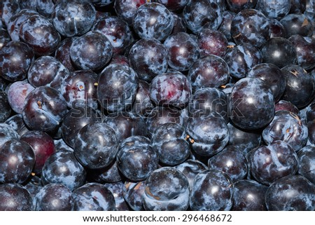 High energy food, health booster juicy ripe plums super fruit on an open air fruit market bazaar. - stock photo
