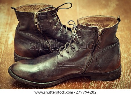 High fashion brown leather men's boots in vintage style on old wooden surface - stock photo