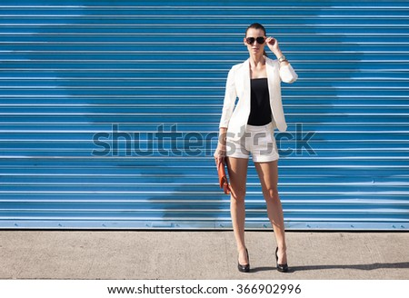 High fashion female model against a blue background.  - stock photo