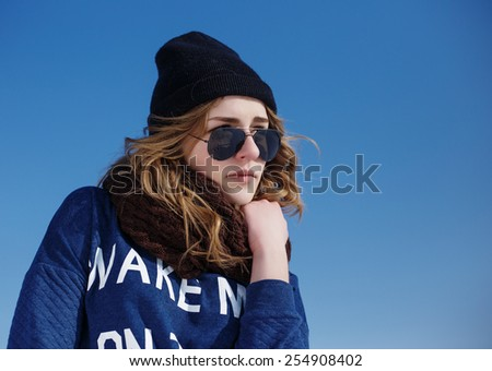 High fashion girl in the sweater and sunglasses outdoor in the winter