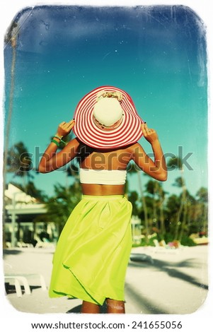 High fashion look. back of glamor sexy model girl  in retro style with palms  in colorful cloth and sunhat behind blue beach  sky - stock photo