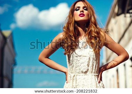 High fashion look.glamor beautiful sexy stylish blond young woman model with bright makeup and pink lips with perfect clean skin in white summer dress in the city behind blue sky - stock photo
