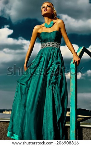 High fashion look.glamor beautiful sexy stylish blond young woman model with bright makeup red lips with perfect sunbathed skin  outdoors in vogue style in evening long blue dress behind sky - stock photo