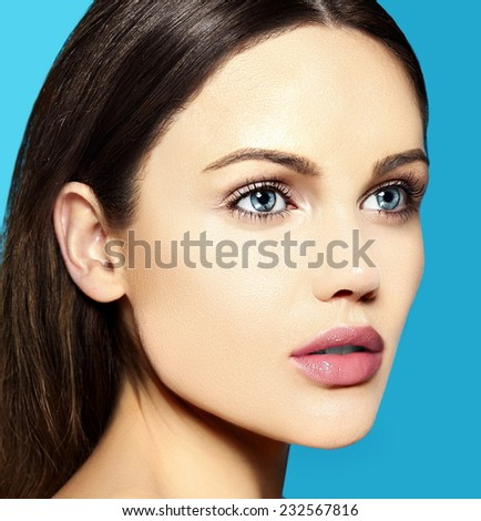 High fashion look.glamor closeup beauty portrait of beautiful sensual  Caucasian young woman model with nude makeup   with perfect clean skin on blue background - stock photo