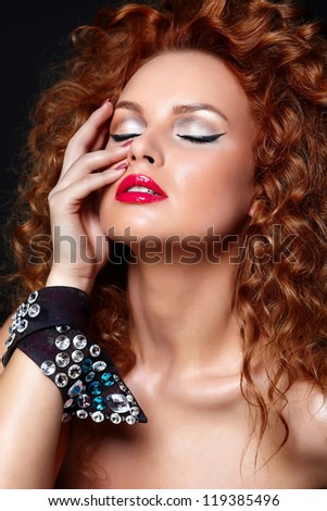 High fashion look.glamor closeup portrait of beautiful sexy redhead Caucasian young woman model with red lips,bright makeup, with perfect clean skin with jewelery isolated on black