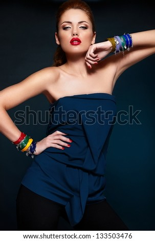 High fashion look.glamor closeup portrait of beautiful sexy stylish blond Caucasian young woman model with bright makeup, with red lips, with perfect clean skin with colorful accessories in blue cloth - stock photo