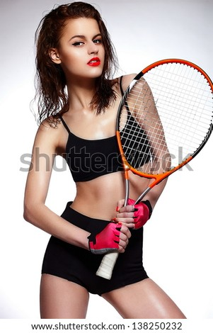 High fashion look.glamor closeup portrait of beautiful sexy stylish brunette Caucasian young professional tennis player woman model with bright makeup, with red lips with racket - stock photo