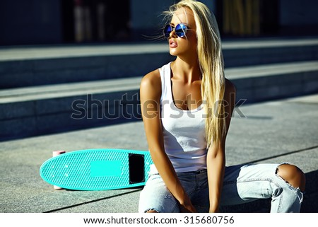 High fashion look.glamor stylish sexy beautiful young blond  model girl in summer bright casual hipster clothes with skateboard sitting in the street - stock photo