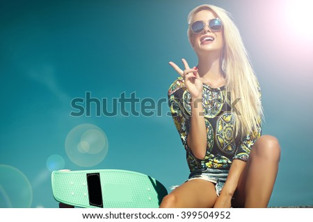 High fashion look.glamor stylish sexy beautiful young blond model girl in summer bright casual hipster clothes with skateboard behind blue sun sky showing her tongue and peace sign - stock photo