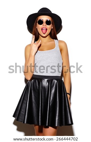 High fashion look.glamor stylish sexy smiling beautiful young woman model in summer bright casual  hipster cloth in hat showing off  tongue giving the Rock and Roll sign - stock photo