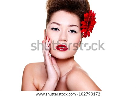 High fashion look.glamour close-up portrait of sexy brunette caucasian young female woman with bright make-up with red lips and red bright manicure with red big flower in hair - stock photo