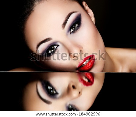 High fashion look.glamour fashion portrait of beautiful sexy brunette girl female model with bright makeup and red lips and her reflection in mirror table on dark with perfect skin - stock photo
