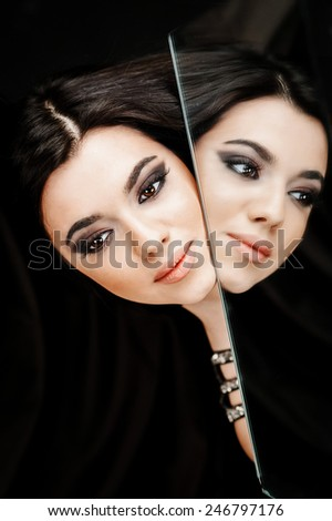 High fashion look.glamour fashion portrait of beautiful sexy brunette girl female model with bright makeup  and her reflection in mirror  on dark with perfect skin - stock photo