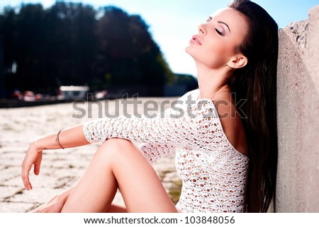 High fashion look.glamour portrait of beautiful sexy brunette female model girl in white lingerie outdoors .blue sky.sitting near sea