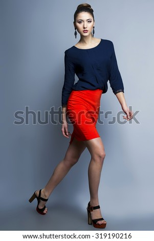 High fashion look of a running girl. Portrait of a fashionable model with sexy red lips, beautiful red skirt and blue shirt. Studio shot - stock photo