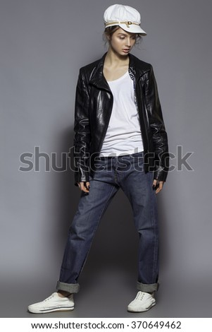 High fashion look. Portrait of a fashionable model with natural make up and perfect skin, dressed in men's jeans, white shirt, black jacket, stylish white hat and sneakers.  Studio shot
