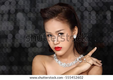 High-fashion Model Girl Beauty Woman Vogue Style Portrait fashionable Luxury lady jewelry diamond earrings necklace Stylish Make up Perfect skin red lips blurred lights Bokeh