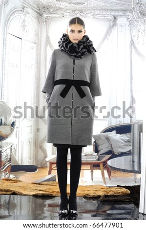 High fashion model in autumn/winter clothes posing in the studio - stock photo