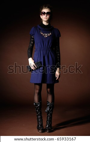 High fashion model in fashion dress wearing sunglasses posing in the studio - stock photo