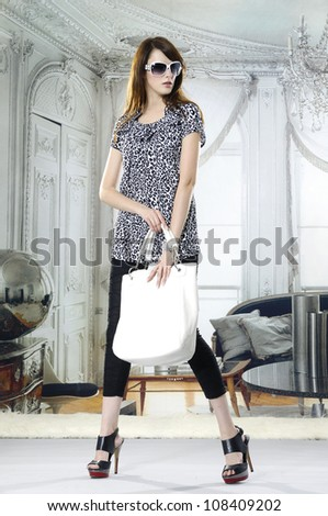 High fashion model in sunglasses with bag posing in the studio