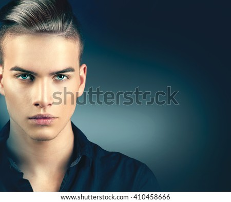 High Fashion model man portrait isolated on dark background. Handsome guy closeup. Stylish haircut, hairstyle. Hair style. Vogue style image of elegant boy - stock photo