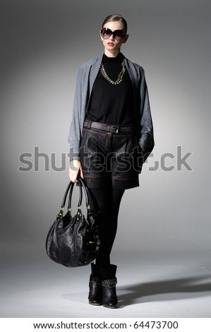 High fashion model with bag posing in light the studio - stock photo