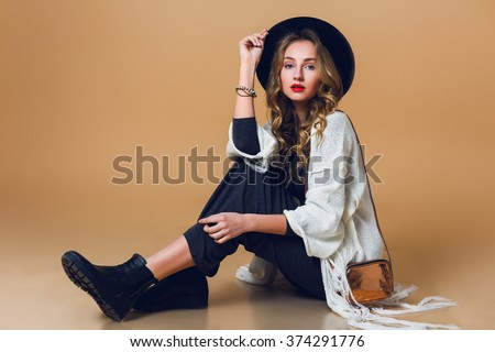 High fashion portrait of young elegant blonde  woman in black wool hat  wearing oversize white fringe  poncho with long grey dress. Studio shot. American hippie bohemian style.   - stock photo