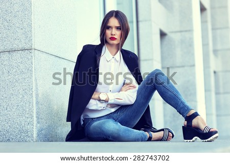 high fashion portrait of young elegant woman outdoor in blue jacket, blouse, jeans. - stock photo