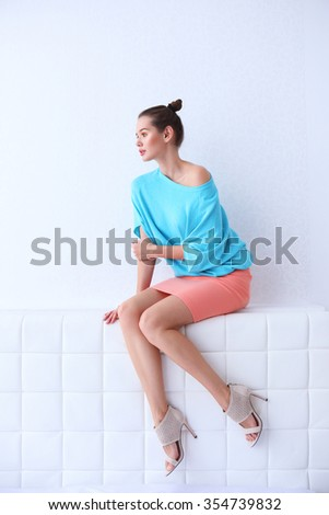 High fashion portrait of young elegant woman. Turquoise blouse, coral skirt, sitting in elegant white interior - stock photo