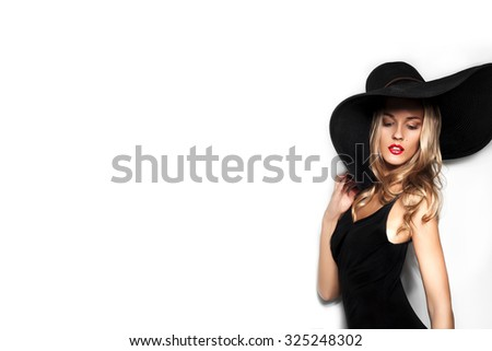 High fashion shot of blonde woman with curly hair in black hat and stylish elegant evening dress posing on white studio background