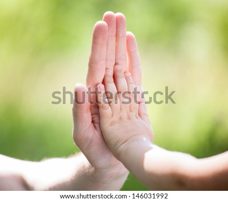 High five gesture of father and child on light freen background - stock photo