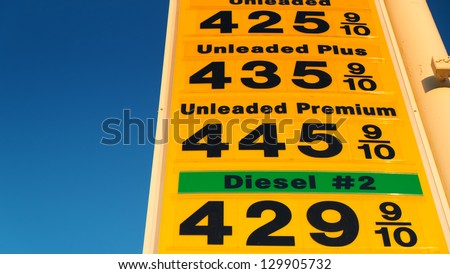 High gas prices on yellow sign over blue sky. - stock photo