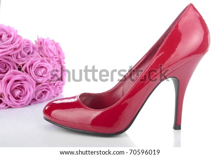 High heel red shoes and flowers on white - stock photo