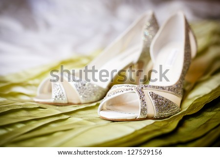 high heel wedding shoes on green satin background - stock photo