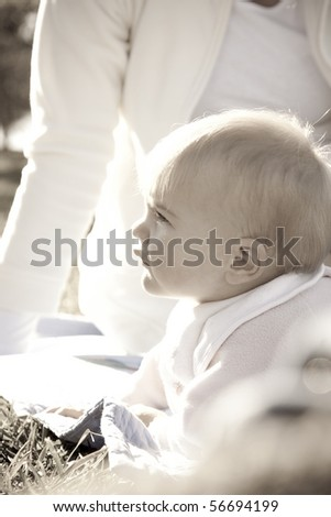 High key image of a baby enjoying the sun in a park with her mother - stock photo
