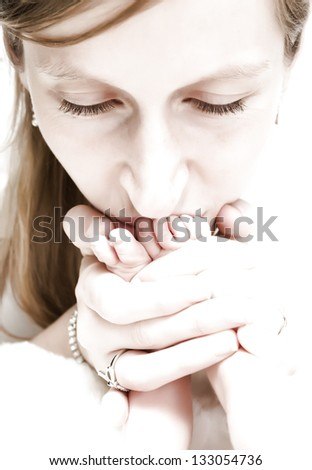 High key image of a tender young mother kissing the feet of her newborn baby - stock photo