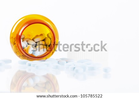 High key image showing pills spilling from a bottle with reflections and ample white copy space on right side.