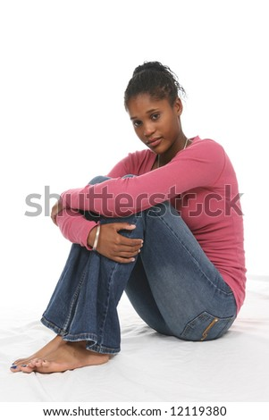 High Key portrait of a pretty teenage girl sitting with her arms around her knees.