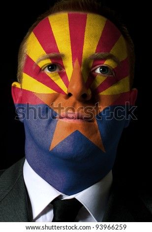 High key portrait of a serious businessman or politician whose face is painted in american state of west arizona flag - stock photo