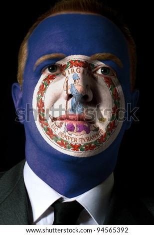 High key portrait of a serious businessman or politician whose face is painted in american state of virginia flag - stock photo