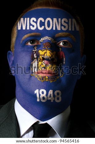 High key portrait of a serious businessman or politician whose face is painted in american state of west wisconsin flag - stock photo