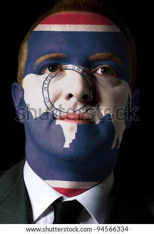 High key portrait of a serious businessman or politician whose face is painted in american state of west wyoming flag - stock photo