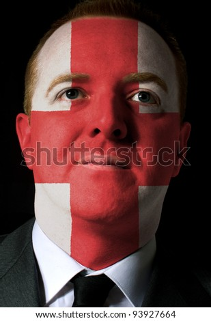 High key portrait of a serious businessman or politician whose face is painted in national colors of england flag