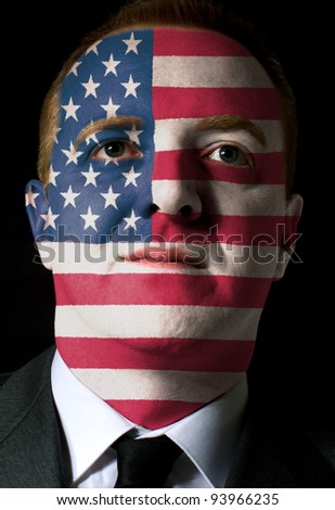 High key portrait of a serious businessman or politician whose face is painted in national colors of american flag - stock photo