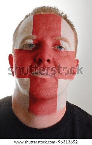 High key portrait of a serious man whose face is painted in national colors of england